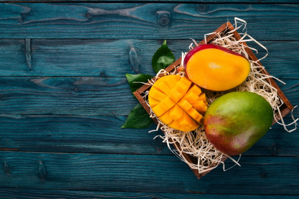 Mango fruits on a wooden background.