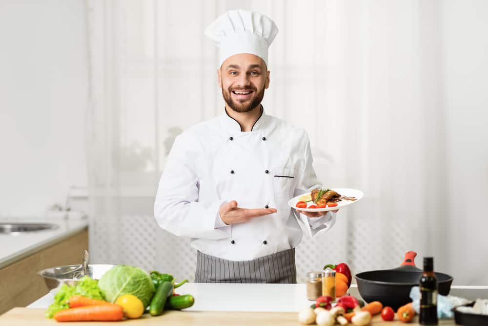Chef Holds Dish In a Kitchen