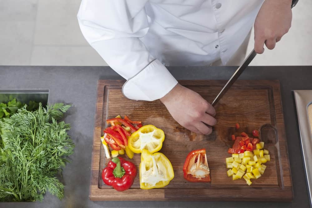 Vegetables being chopped on wooden board