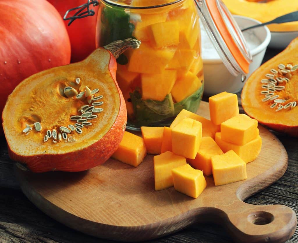 Chopped pumpkin on rustic cutting board and ingredients for tasty vegetarian cooking, dark styled .