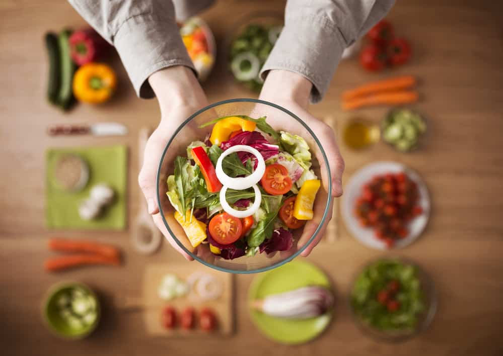 Hands holding an healthy fresh vegetarian salad in a bowl, fresh raw vegetables on background