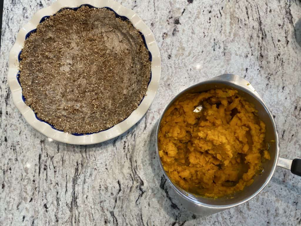 Pie plate with nut crust and cooked squash in a pot on a marble kitchen counter.