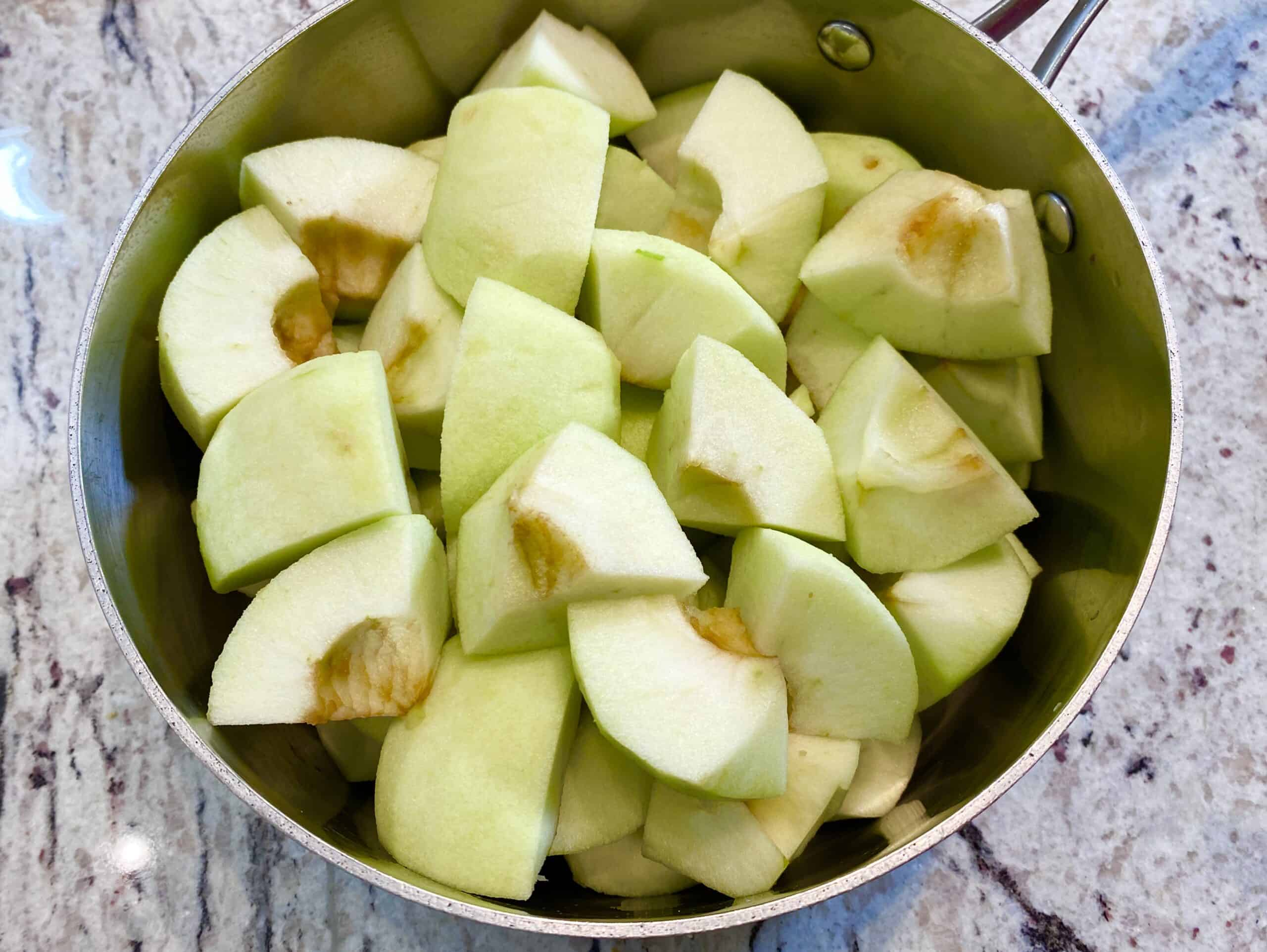 Chopped apples in a saucepan on the kitchen counter.