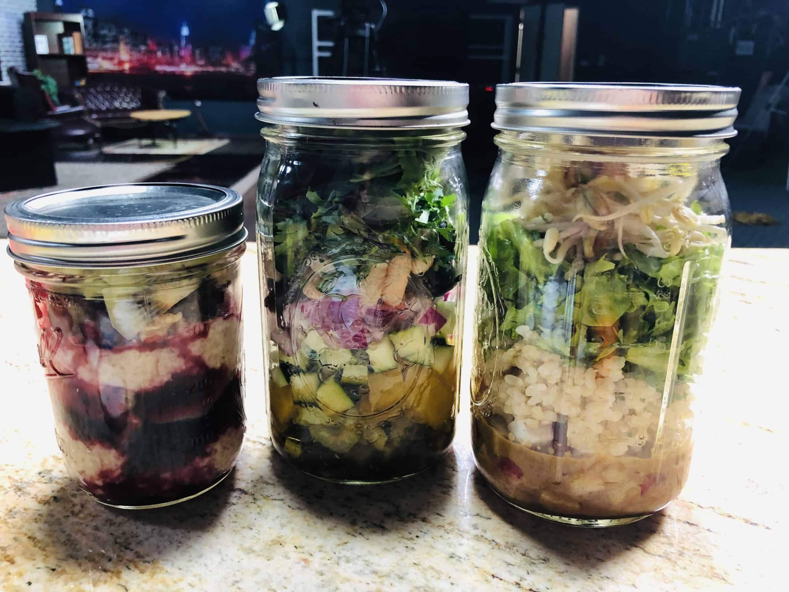 Three mason jar meals prepped wit rice and vegetables for healthy plant-based meal prep