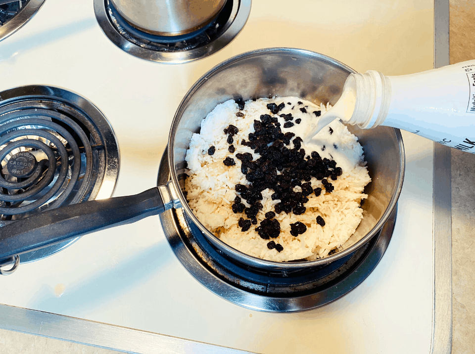 almond milk, rice and raisins in pan