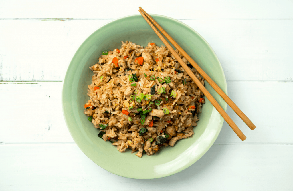 Chinese fried rice in a green bowl with chopsticks