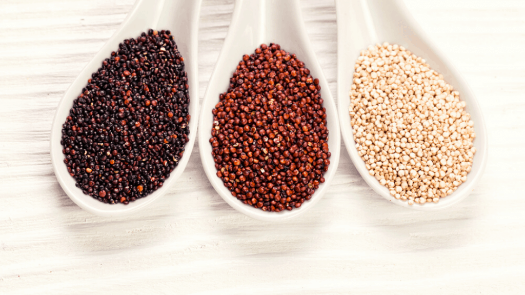 black, red and white quinoa grains on a wooden background