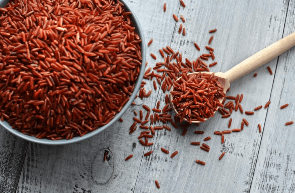 Red rice in a bowl and wooden spoon